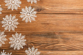 top view of winter snowflakes on wooden background