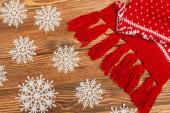 vrchní pohled na zimní sněhové vločky a červenou pletenou šálu na dřevěném pozadí