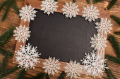 top view of winter snowflakes on chalkboard on wooden background