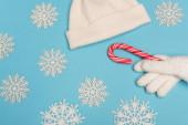 Draufsicht auf weiße Strickwaren, Zuckerrohr und Schneeflocken auf blauem Hintergrund