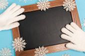 vrchní pohled na zimní bílé rukavice, tabuli a sněhové vločky na modrém pozadí