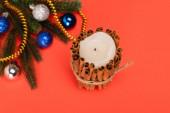 vrchní pohled na zdobené vánoční stromeček a svíčka na červeném pozadí