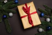 Draufsicht auf geschmückten Weihnachtsbaum und Geschenk auf schwarzem Hintergrund