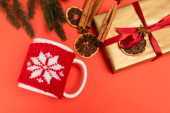 top view of Christmas tree, gift with spices and mug on red background