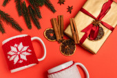 vrchní pohled na vánoční stromek, dárek s kořením a hrnky na červeném pozadí