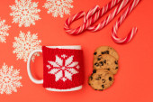 Photo top view of chocolate  cookies, candy canes, snowflakes and mug on red background