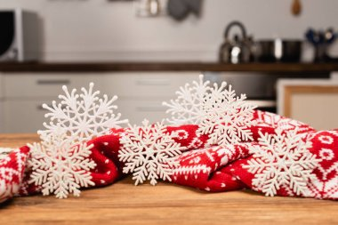 Winter snowflakes and knitted red scarf on wooden table stock vector