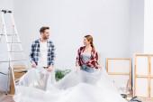 boldog fiatal pár polietilén nézik egymást, miközben borító szoba felújítása során lakás