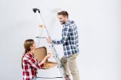 usmívající se mladý muž s válcovým malba stěna při pohledu na ženu dávat kus pizzy v blízkosti žebříku izolované na šedé