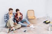 plná délka mladých párů jíst pizzu, zatímco sedí v blízkosti notebooku na podlaze doma