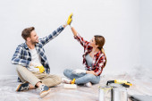 full length of happy young couple in gloves giving each other high five while sitting on floor near tins of paint at home
