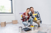 full length of happy young couple with rollers looking at camera while squatting near tins of paint and tray at home