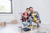 teljes hossza boldog fiatal pár görgők nézi a kamerát, miközben guggoló közelében dobozok festék és tálca otthon