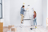 full length of smiling young couple with rollers painting wall and looking at each other near ladder at home