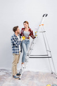 full length of smiling young man hugging woman with paint roller standing on ladder at home