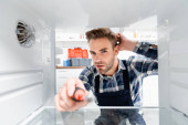 Photo young thoughtful repairman with screwdriver looking at camera in freezer on blurred foreground