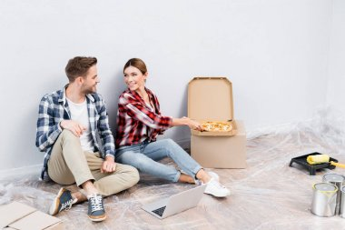 Full length of smiling young woman giving piece of pizza to man near laptop on floor stock vector