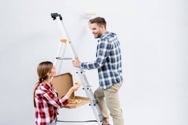 Smiling young man with roller painting wall looking at woman giving piece of pizza near ladder isolated on grey stock vector