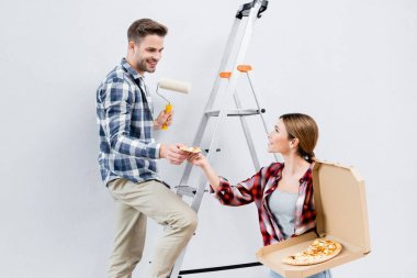 Happy young man taking piece of pizza from woman near ladder isolated on white stock vector