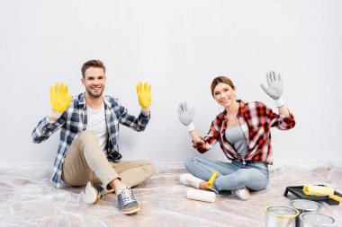 Full length of happy young couple looking at camera and showing gloves while sitting on floor at home stock vector