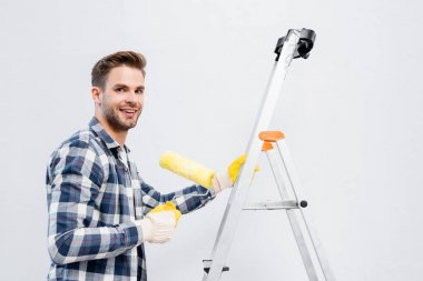 Happy young man looking at camera while holding paint roller on ladder isolated on white stock vector