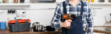 Cropped view of handyman holding drill on blurred background in kitchen, banner stock vector