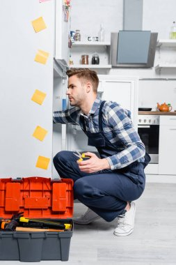 Buzdolabını tamir eden genç bir tamirci. Mutfaktaki açık alet çantasının yanında oturuyor.