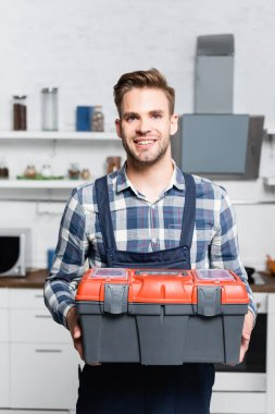 Front view of happy repairman looking at camera while holding toolbox with blurred kitchen on background stock vector