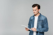 Young man in denim jacket using digital tablet isolated on grey