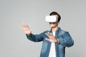 Smiling man playing video game in virtual reality headset isolated on grey