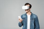 Usmívající se muž vr sluchátka pomocí smartphone izolované na šedé