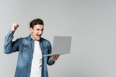 Cheerful man showing yeah gesture while holding laptop isolated on grey stock vector