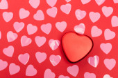 top view of pink hearts and box on red background