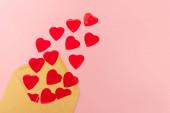 horní pohled na červená srdce a obálka na růžovém pozadí