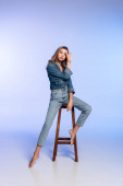 okouzlující žena v džínové oblečení dotýkat vlasy, zatímco sedí na vysoké stoličce na modré