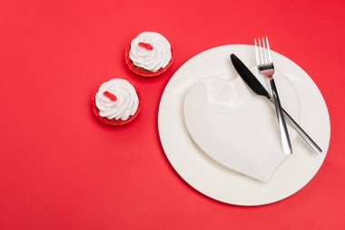 Top view of cupcakes near plate with cutlery on red background stock vector