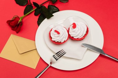 Cupcakes on plate near rose and envelope on red background stock vector