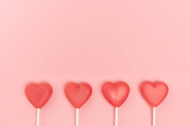 Top view of heart shaped lollipops on pink background stock vector