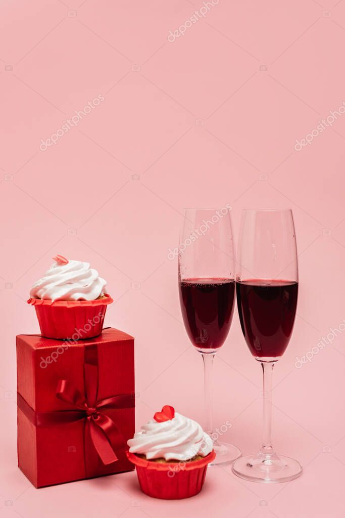Red wine near gift and cupcakes isolated on pink stock vector