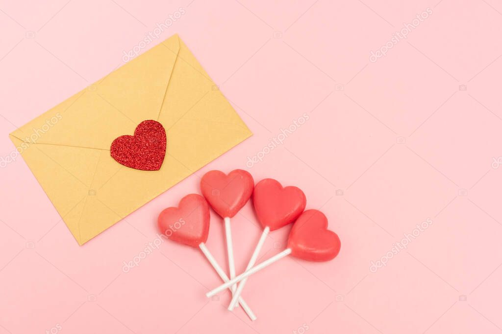 Top view of heart shaped lollipops and envelope with heart on pink background stock vector