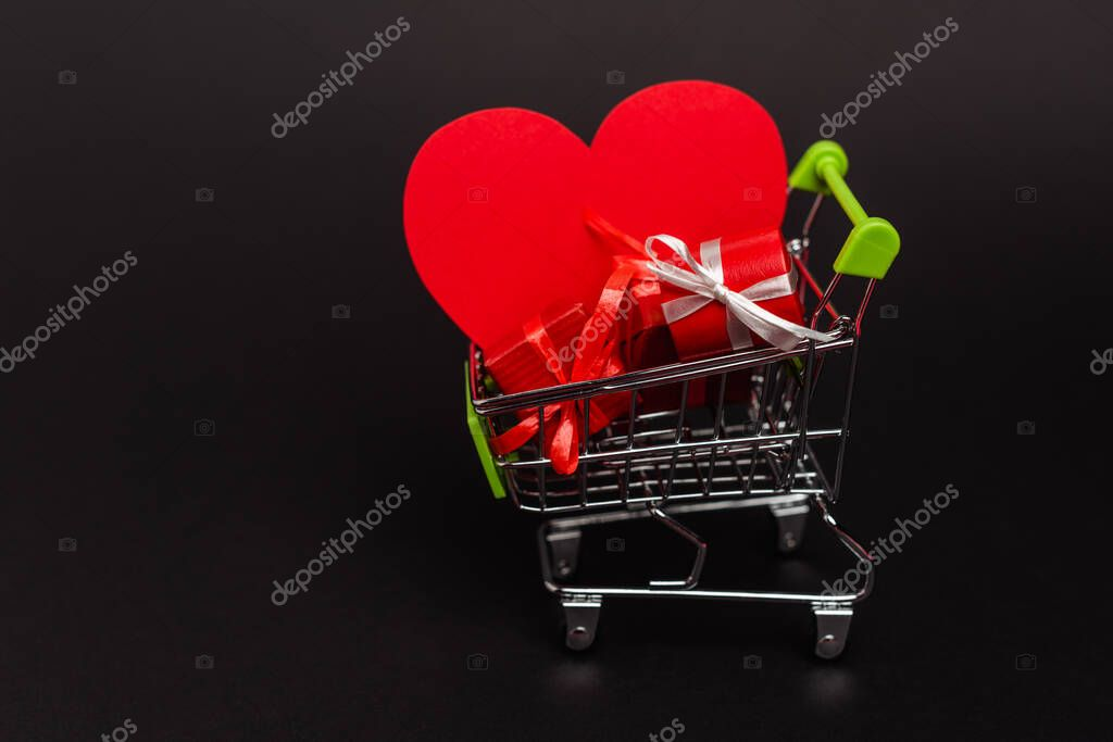 Shopping cart with valentines gifts and heart isolated on black stock vector