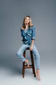 svůdná, bosá žena ve stylových džínových šatech sedící na vysoké stoličce a dotýkající se šedé tváře