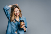 Photo smiling woman in denim shirt touching hair while holding coffee to go isolated on grey