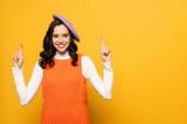 Šťastná brunetka žena v baretu se zkříženými prsty při pohledu na kameru izolované na žluté