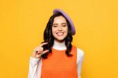 Usmívající se brunetka žena v baretu ukazuje malé množství gesta při pohledu na fotoaparát izolované na žluté