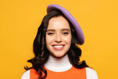 Portrait of smiling brunette woman in beret looking at camera isolated on yellow stock vector