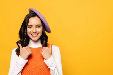 Cheerful brunette woman in beret showing thumbs up while looking at camera isolated on yellow stock vector