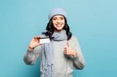 Boldog barna nő téli ruhában hitelkártya mutatja hüvelykujját felfelé, miközben néz kamera elszigetelt kék