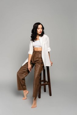 Full length of curly brunette woman in shirt and leather pants looking away while posing on stool on grey background stock vector