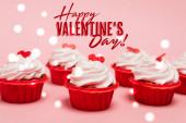 chutné cupcakes s červenými srdci v blízkosti šťastný Valentines den nápis na růžové pozadí
